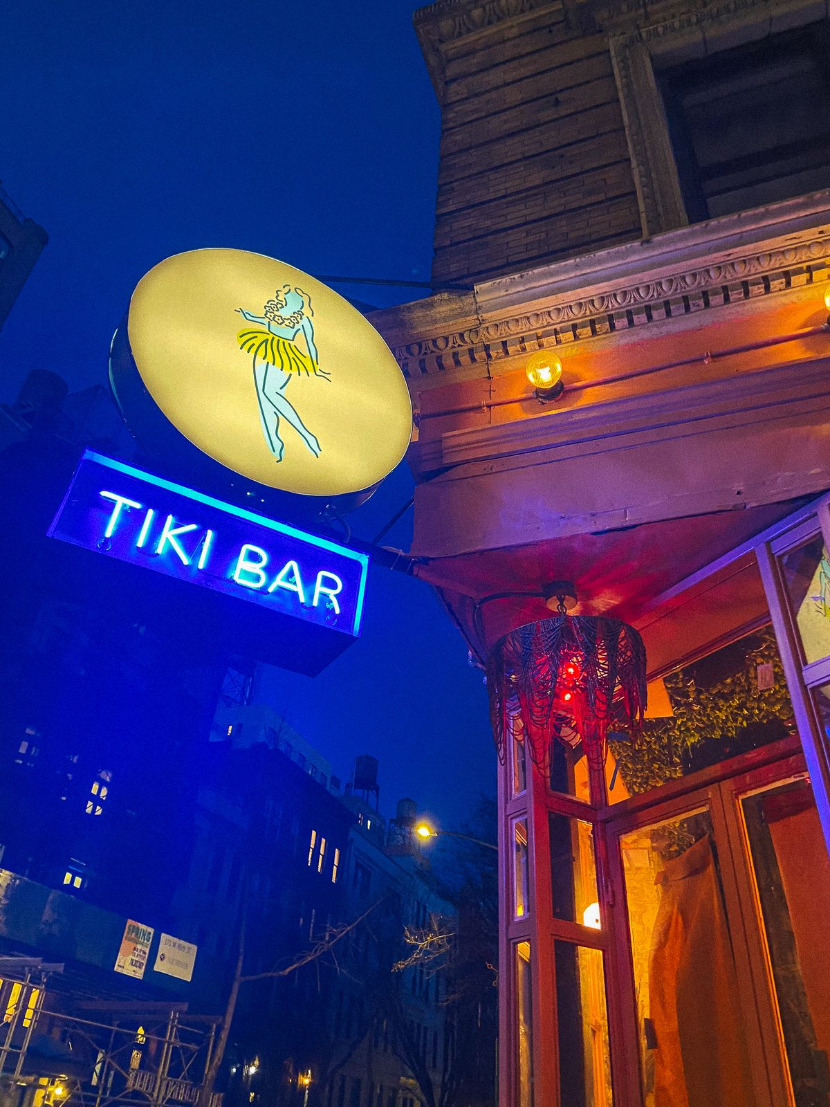 A blue neon sign reads tiki chick. Above it is a round sign with a woman wearing a lei and a hula skirt.