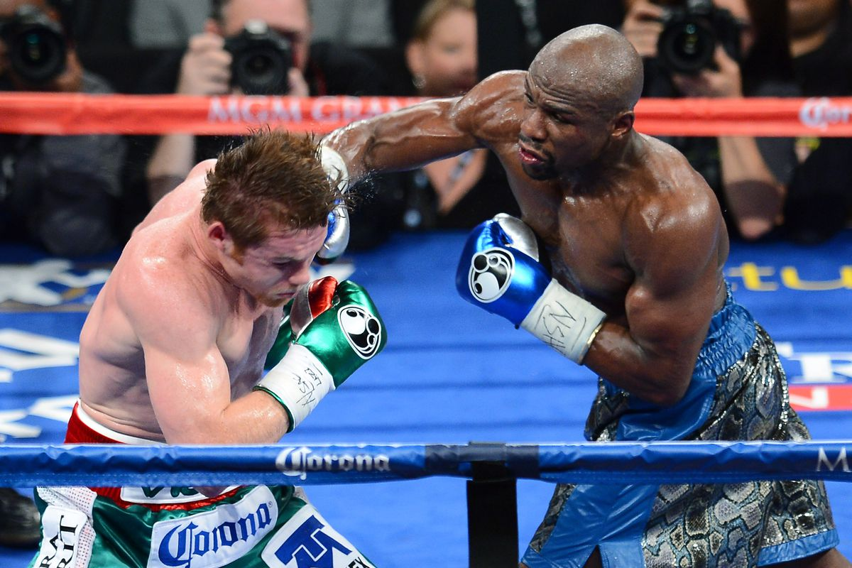 Floyd Mayweather Jr. (R) hits Canelo Alvarez in the fifth round of their WBC/WBA 154-pound title fight at the MGM Grand Garden Arena on September 14, 2013 in Las Vegas, Nevada.