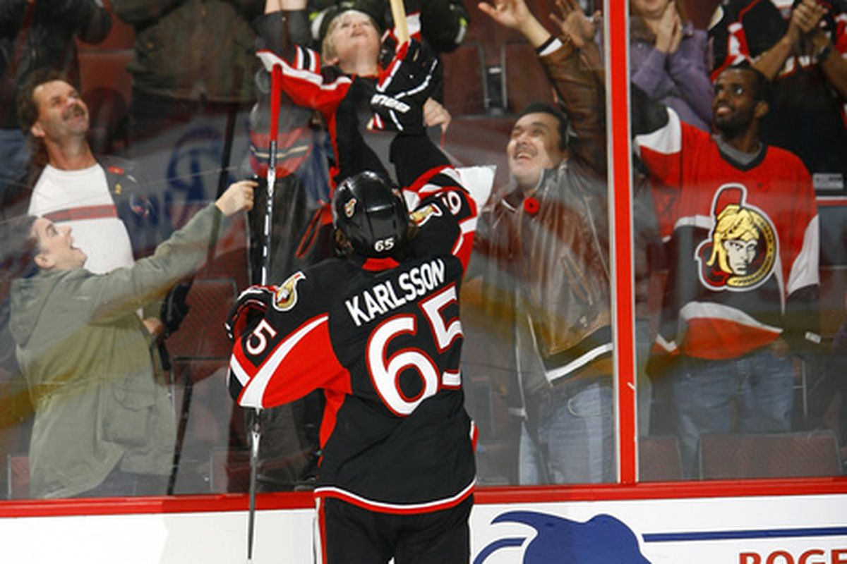 Erik Karlsson of the Ottawa Senators teases a child by mercilessly holding a stick out of his reach.
