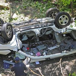 Police investigate the destroyed van that plunged over the Bronx River Parkway, Sunday April 29, 2012, in New York. Authorities say the out-of-control van plunged off a roadway near the Bronx Zoo, killing seven people, including three children.
