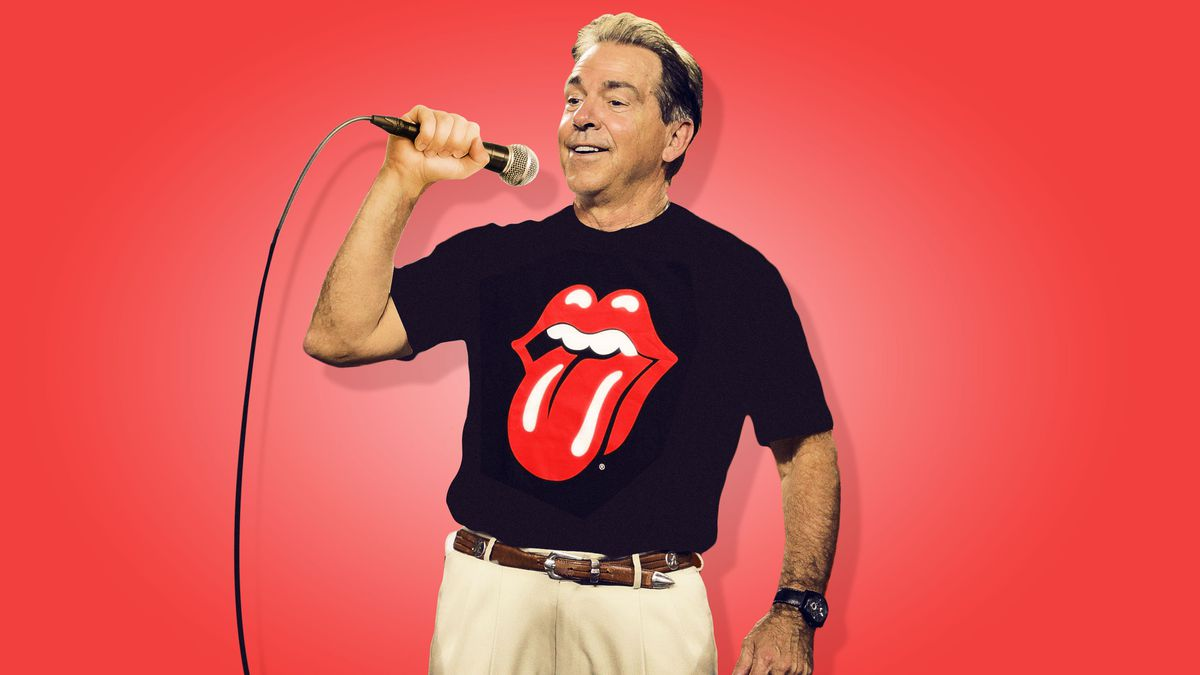 Alabama football coach Nick Saban holding a microphone and wearing a Rolling Stones T-shirt