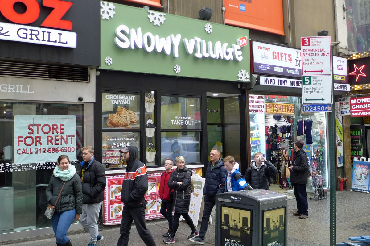 A crowd of tourists passes by the facade of Snowy Village, which is covered with big snowflakes.