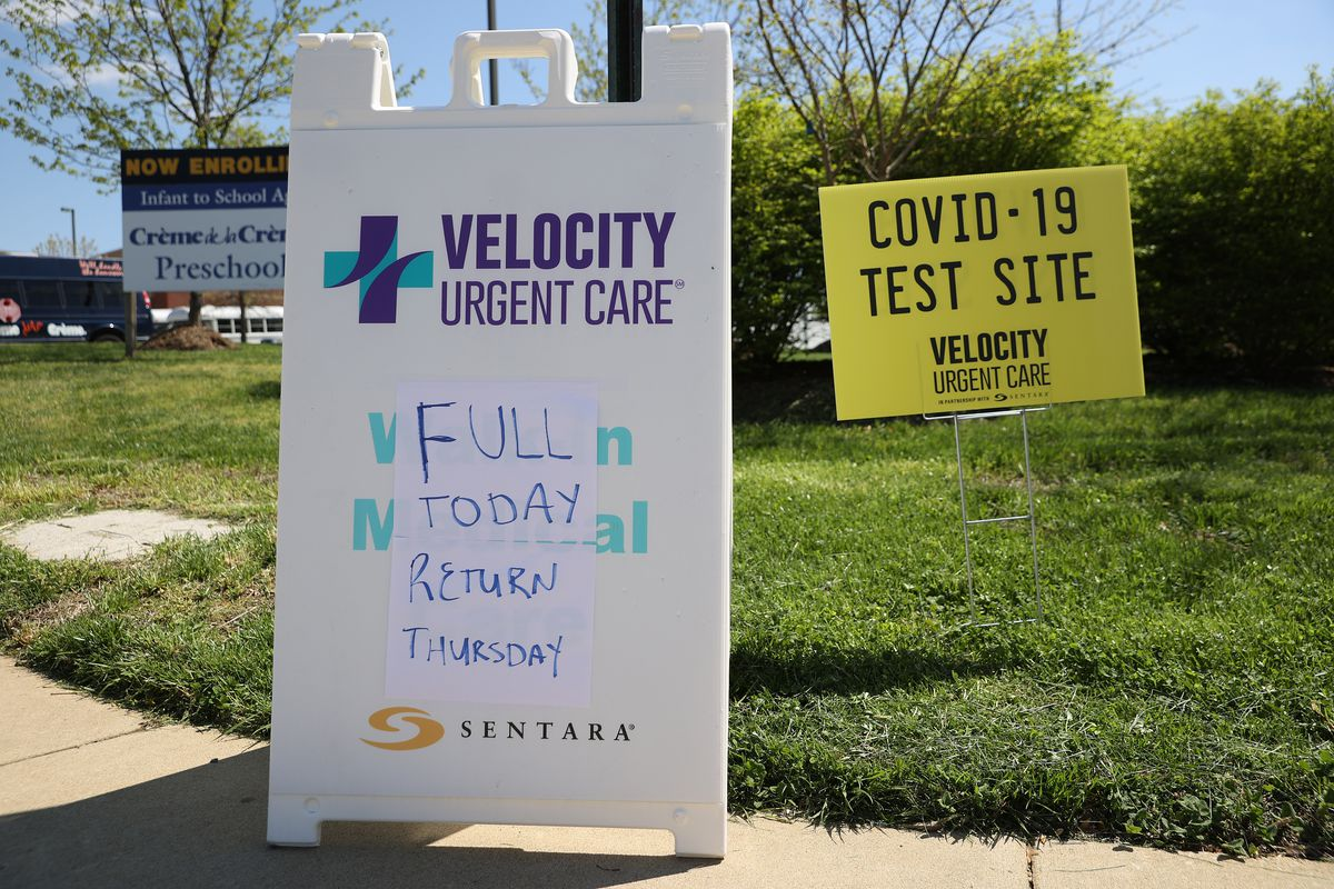 "A sign on the lawn outside an urgent care facility reads, ""Velocity urgent care full today, return Thursday."" Another sign reads, ""Covid-19 test site."""