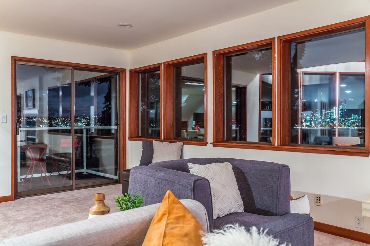 A living room with windows on both visible walls, including a sliding glass door to a view deck. Downtown Seattle is visible through the windows.