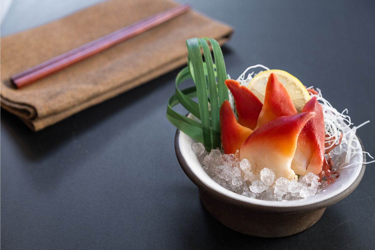 A small bowl filled with clam sashimi, next to a napkin and a pair of chopsticks.