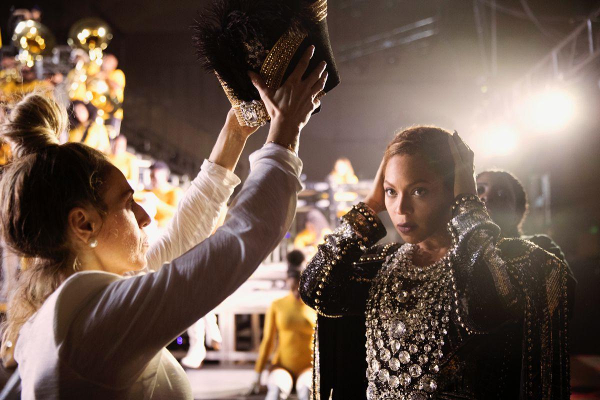 A dresser gives Beyoncé her headdress at her 2018 Coachella performance.