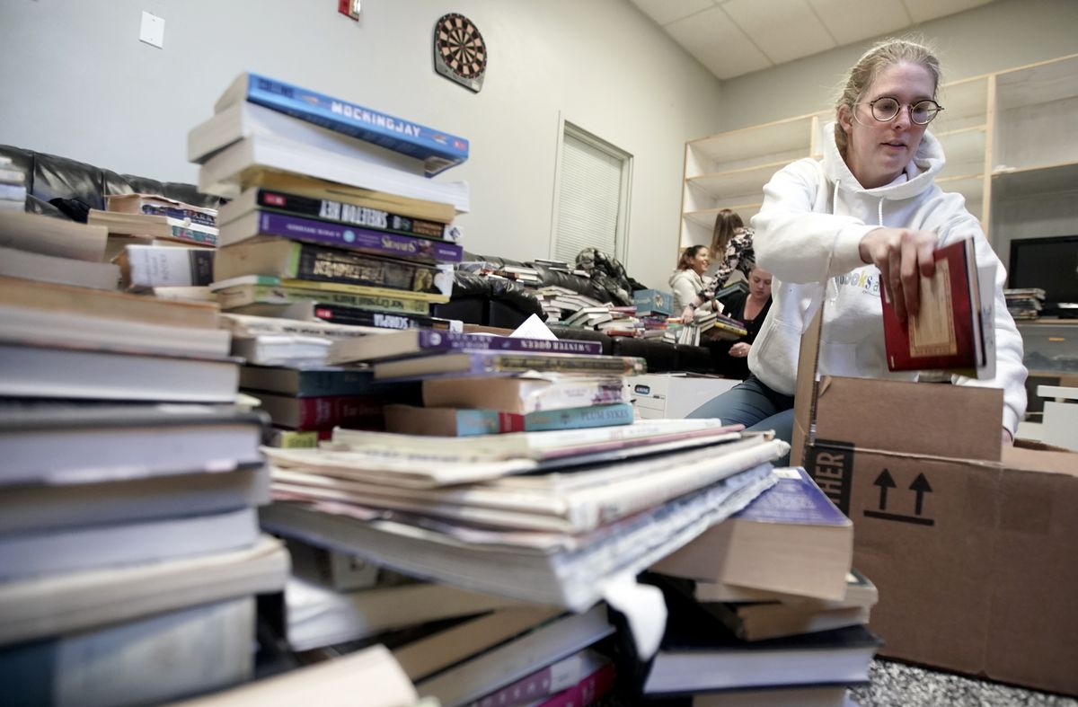 Olivia Wilkinson, Utah State Library cataloguer, boxes up old books to make room for new ones at the Odyssey House Adolescent Residential Center in Salt Lake City on Wednesday, Oct. 30, 2019.Staff from the state library are using a federal grant to redo the library at the center to add age-specific books for the teens in treatment.