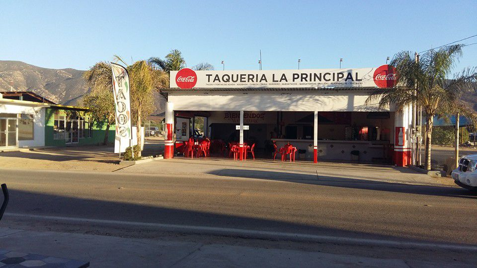 A garage-like restaurant, with a sign reading Taqueria La Principal, sits along a roadside in the sunshine beside palm trees