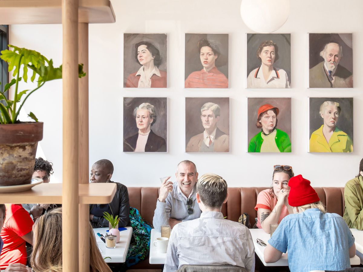 Diners sit in tables in a row with portraits hanging on a wall above them