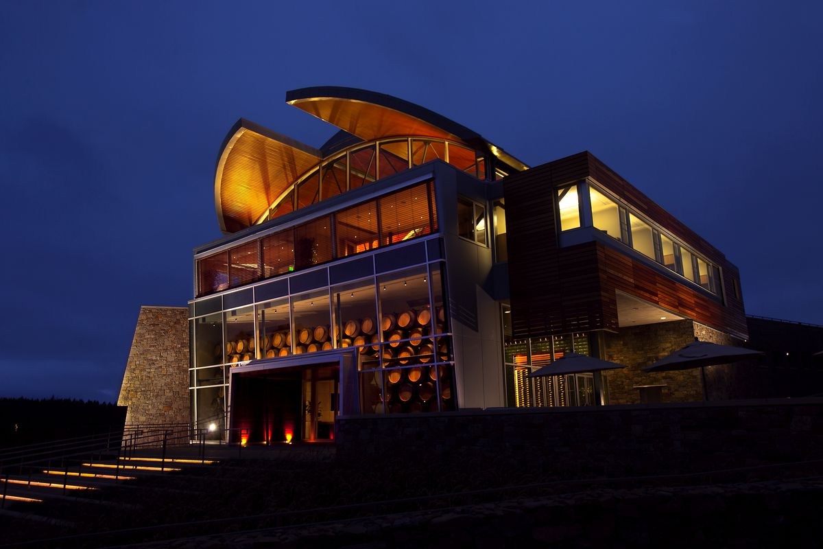 The exterior of the William Selyem Winery in California. The facade is redwood and glass. It is evening and the sky is dark blue.