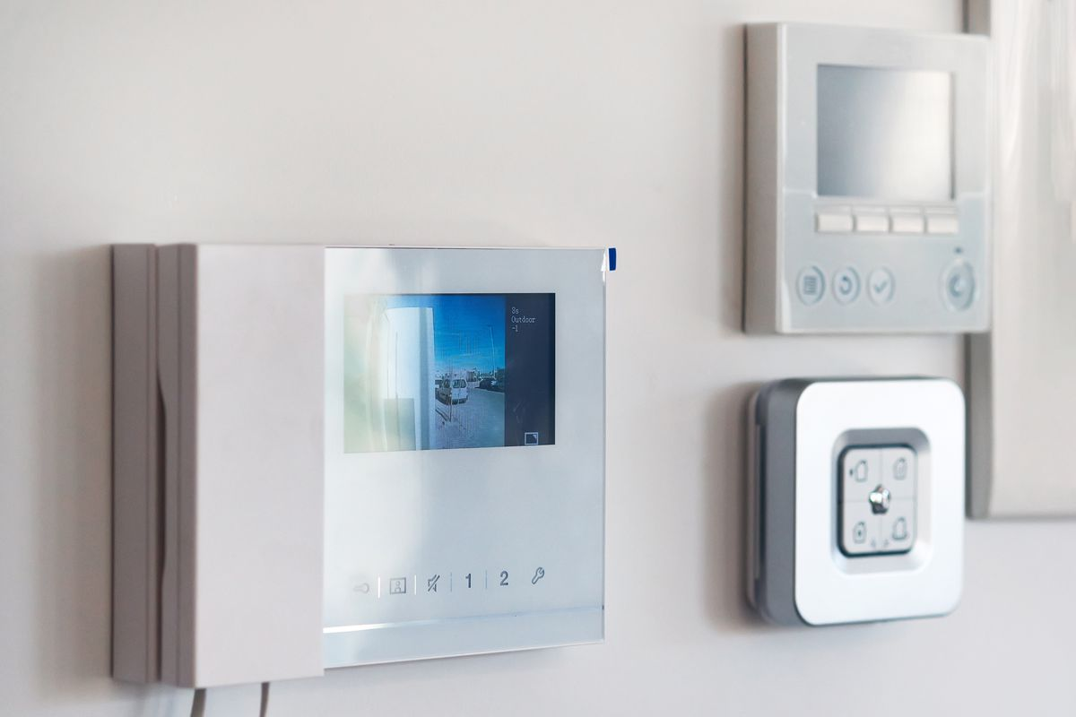 On white wall home security alarm and video intercom.