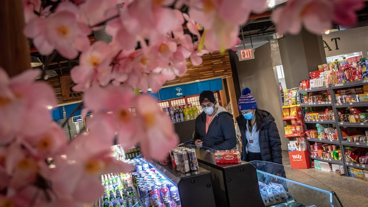 Two people wearing masks stand inside a grocery store, where pink flowers are in the foreground.