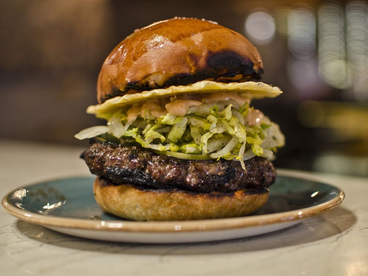 A burger sits on a blue plate, piled high with shredded lettuce, sauce, and a crispy disc of cheese