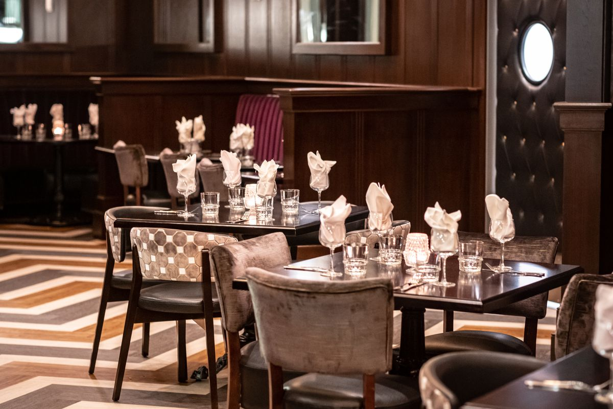 Dining tables dressed with glasses containing tufted napkins sprawl across a chevron-patterned floor