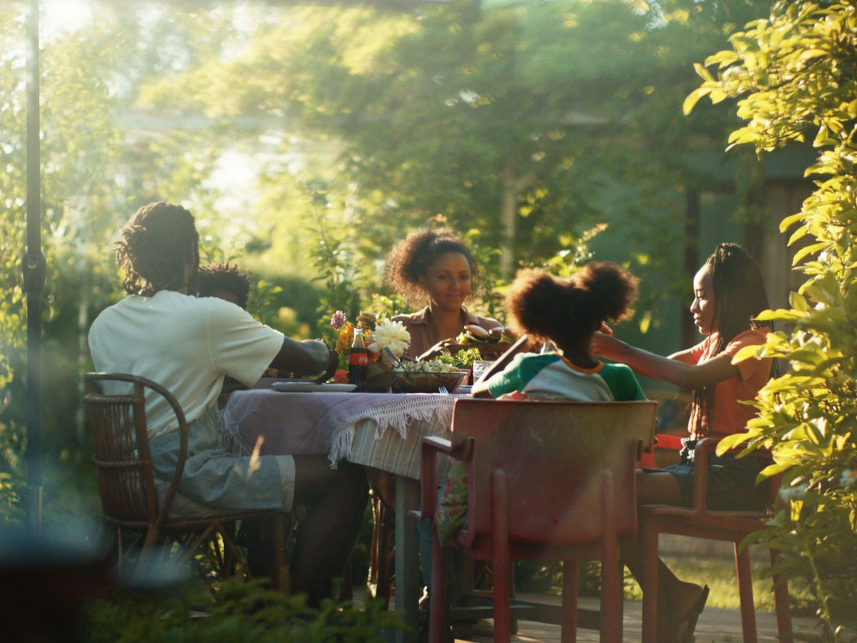 A family of five enjoys a backyard meal at a table amid green trees.