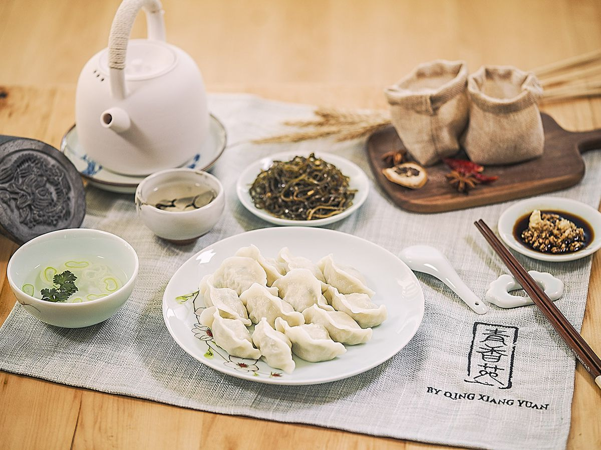 A plate of dumplings alongside sauces, side dishes, a teapot, and utensils.