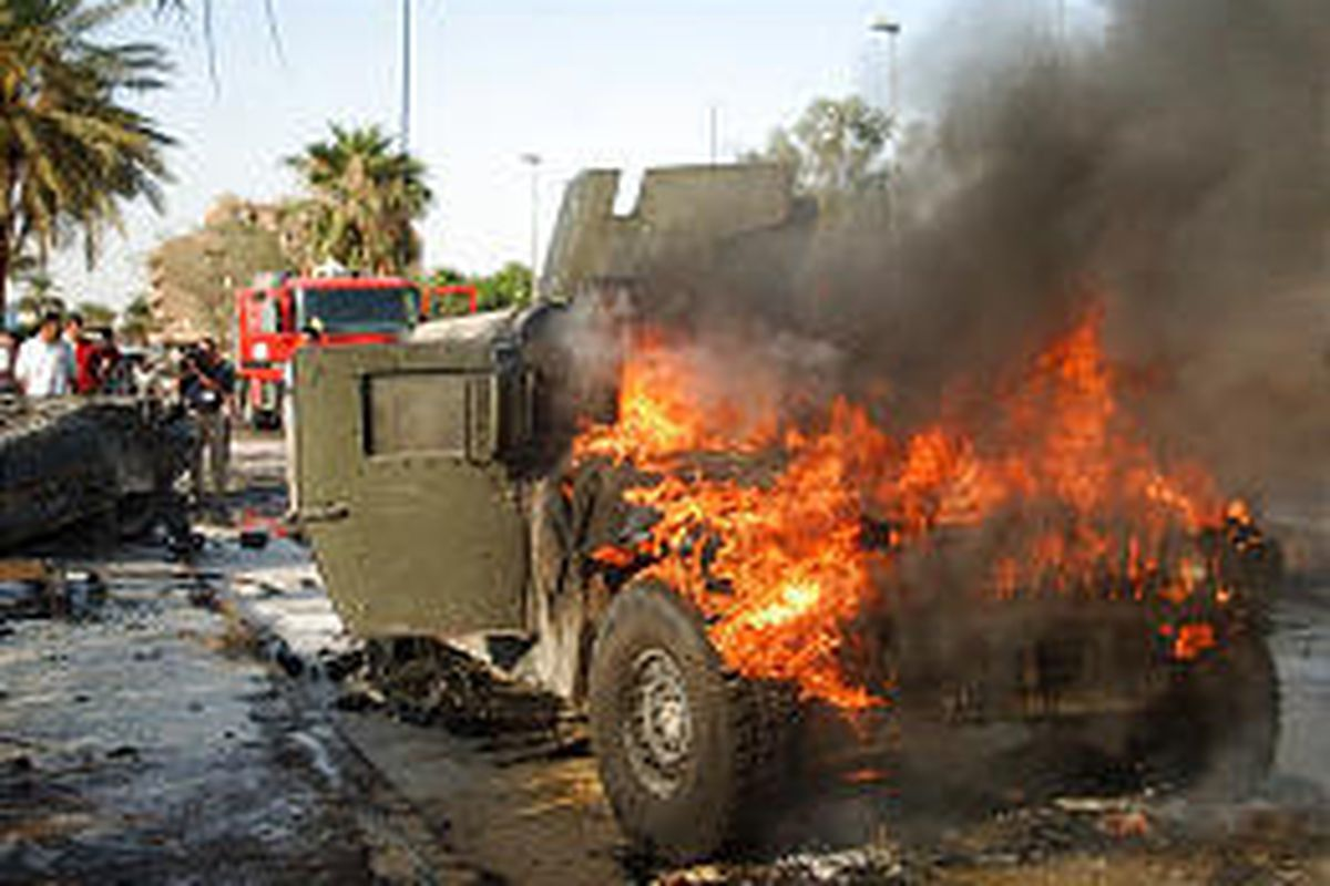 A Humvee ignited by a car bomb burns in Baghdad last month. Convoy duty is one of the U.S. military's most dangerous tasks.
