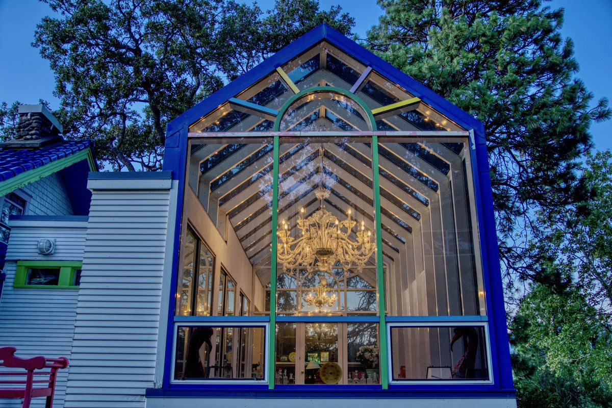 An all glass room features a chandelier and views of the trees.