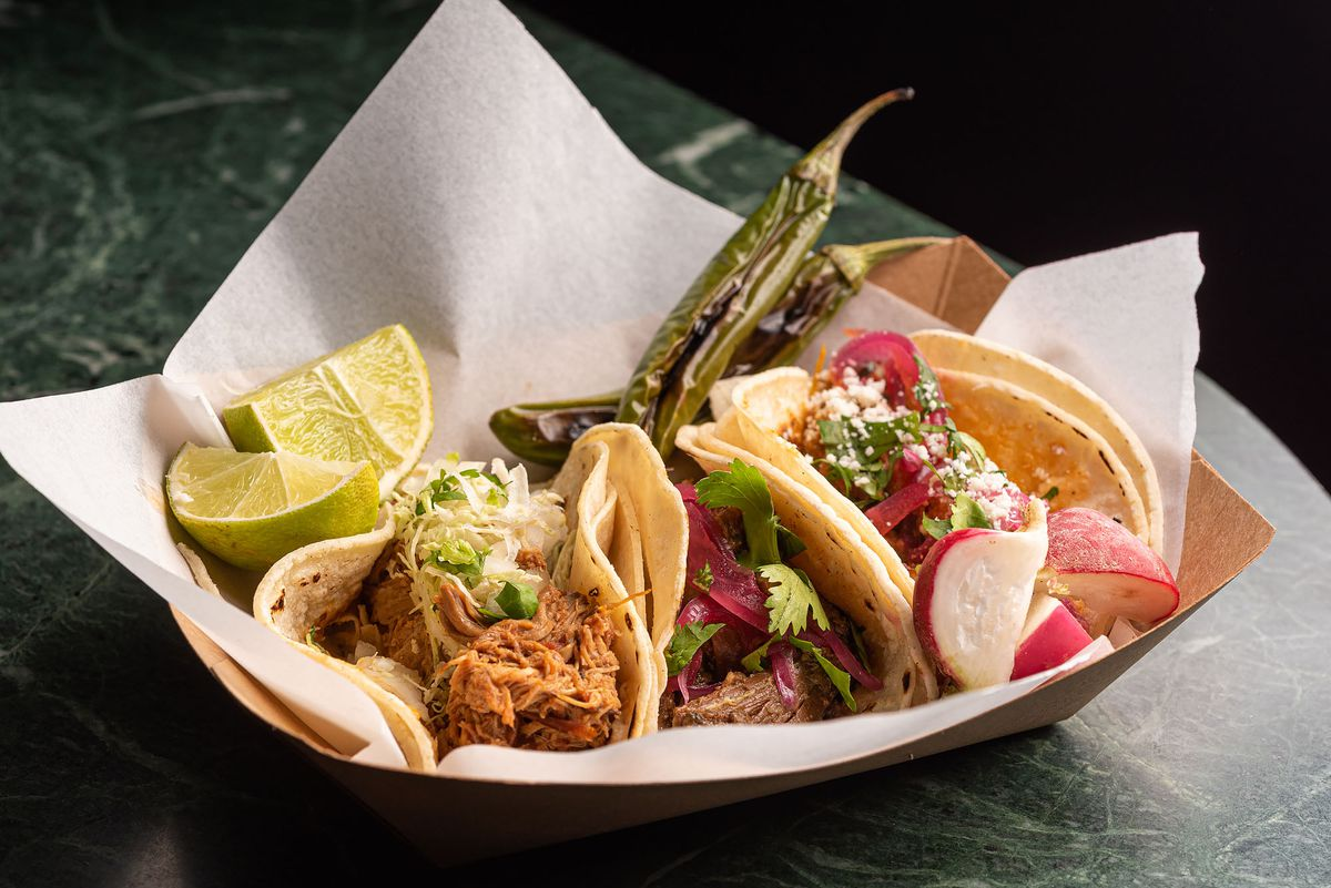 A trio of tacos, including carnitas, at a cocktail bar.