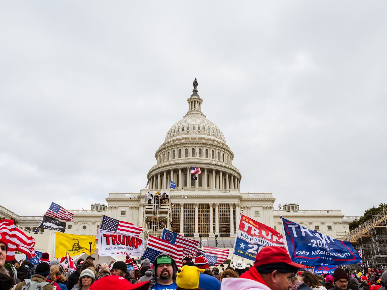 WASHINGTON, DC - JANUARY 06: A large group of pro-Trump protesters raise signs and flags on the grounds of the Capitol Building on January 6, 2021 in Washington, DC. A pro-Trump mob stormed the Capitol earlier, breaking windows and clashing with police officers. Trump supporters gathered in the nation's capital today to protest the ratification of President-elect Joe Biden's Electoral College victory over President Trump in the 2020 election. (Photo by Jon Cherry/Getty Images) ORG XMIT: 775604807
