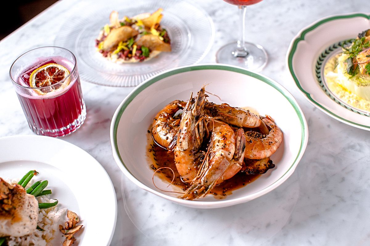 A plate of head-on shrimp is served in a brown barbecue sauce that includes birch beer