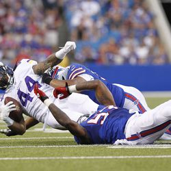 Aug 16, 2013; Orchard Park, NY, USA; Minnesota Vikings running back Matt Asiata (44) is tackled by Buffalo Bills outside linebacker Nigel Bradham (53) and defensive tackle Alan Branch (90) during the second quarter at Ralph Wilson Stadium.