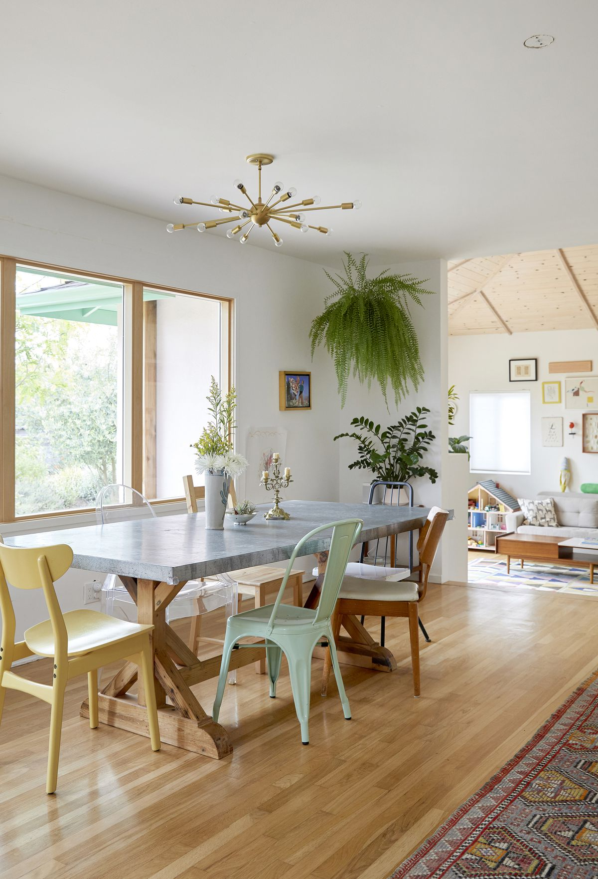 A dining room with a large table and a variety of chairs. The floor is exposed wood. There is a light fixture and a hanging houseplant. A large window faces the table and overlooks the outside.