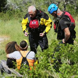 A member of the Salt Lake County Search and Rescue team talks with relatives of a 22-year-old hiker who fell in Bell Canyon as crews work to recover the body on Monday, June 5, 2017. Siaosi Brown's body was spotted in the lower falls of the canyon. His body was trapped on some logs in the middle of the waterfall, Unified Police Lt. Brian Lohrke said.
