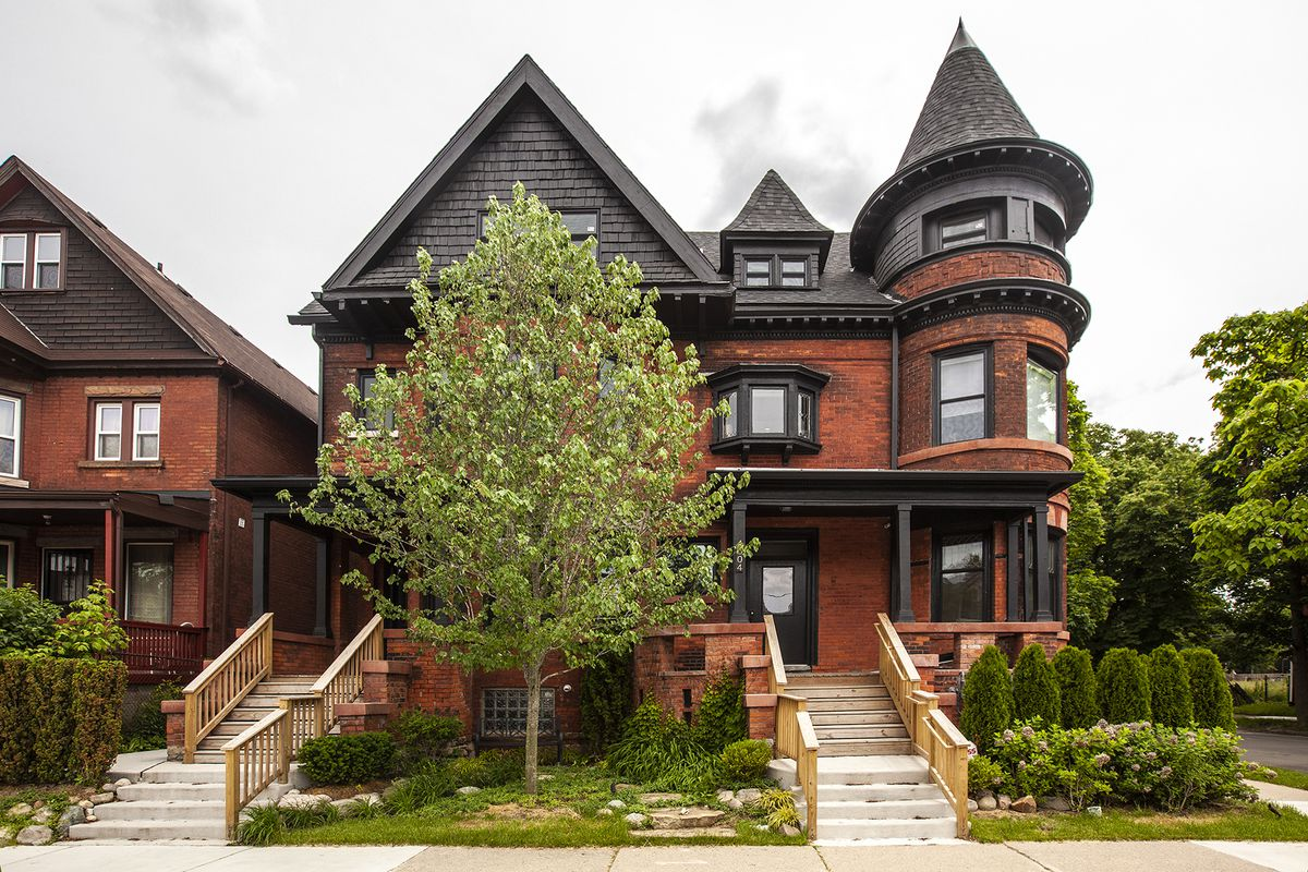 A three-story brick home with black-painted wood around the porch, window frames, and roof.