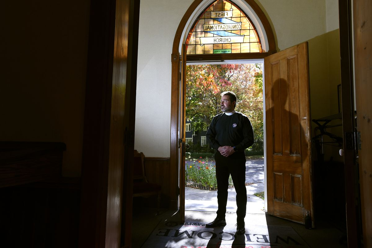 The Rev. Salvatore Sapienza stands in the doorway of the historic Douglas Congregational United Church of Christ in the village of Douglas, Mich., on Tuesday Oct. 13, 2020. As part of the Our Faith Our Vote 2020 initiative, volunteers at the church will drive voters with their completed mail-in ballots to the county clerk's office to drop them off in person. The drivers and voters will be masked and separated in vehicles to minimize any COVID-19 risk.