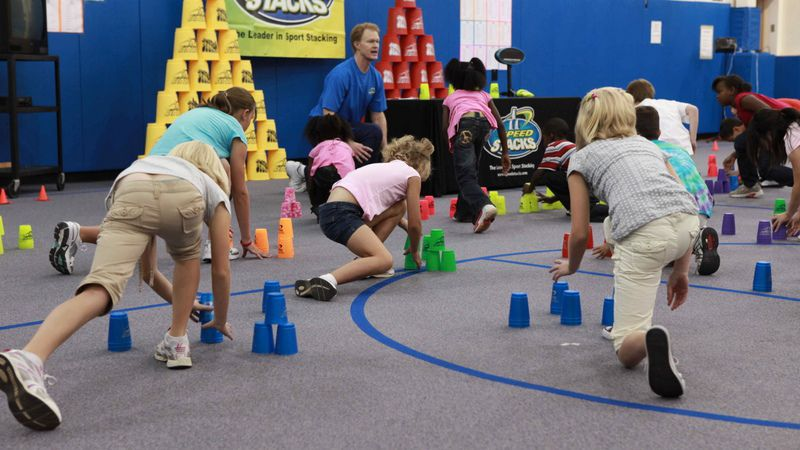 Sport stacking involves stacking up and taking down 12 specially designed cups. PE teachers often add relay races or other activity.