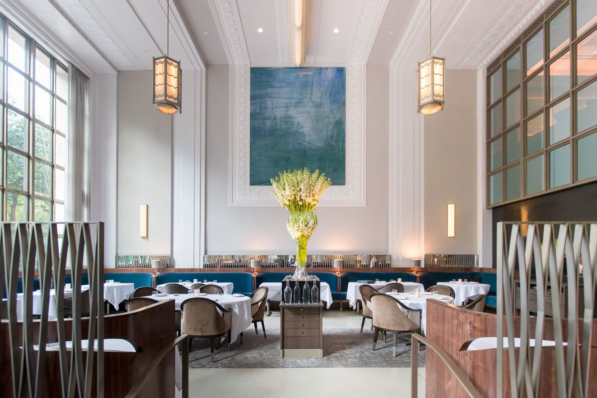 A high-ceilinged, elegant dining room with a blue painting hanging in the back.