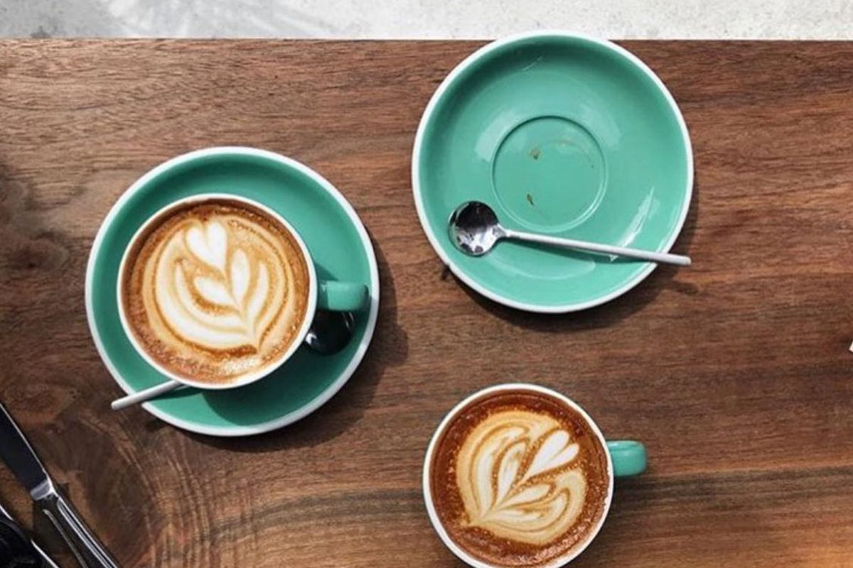 two cups of latte coffees on turquoise saucers