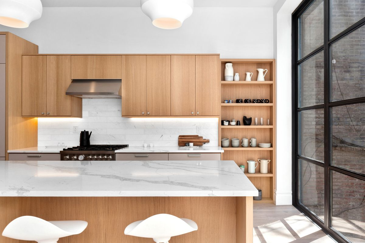 An open kitchen with a large island and white cabinetry.