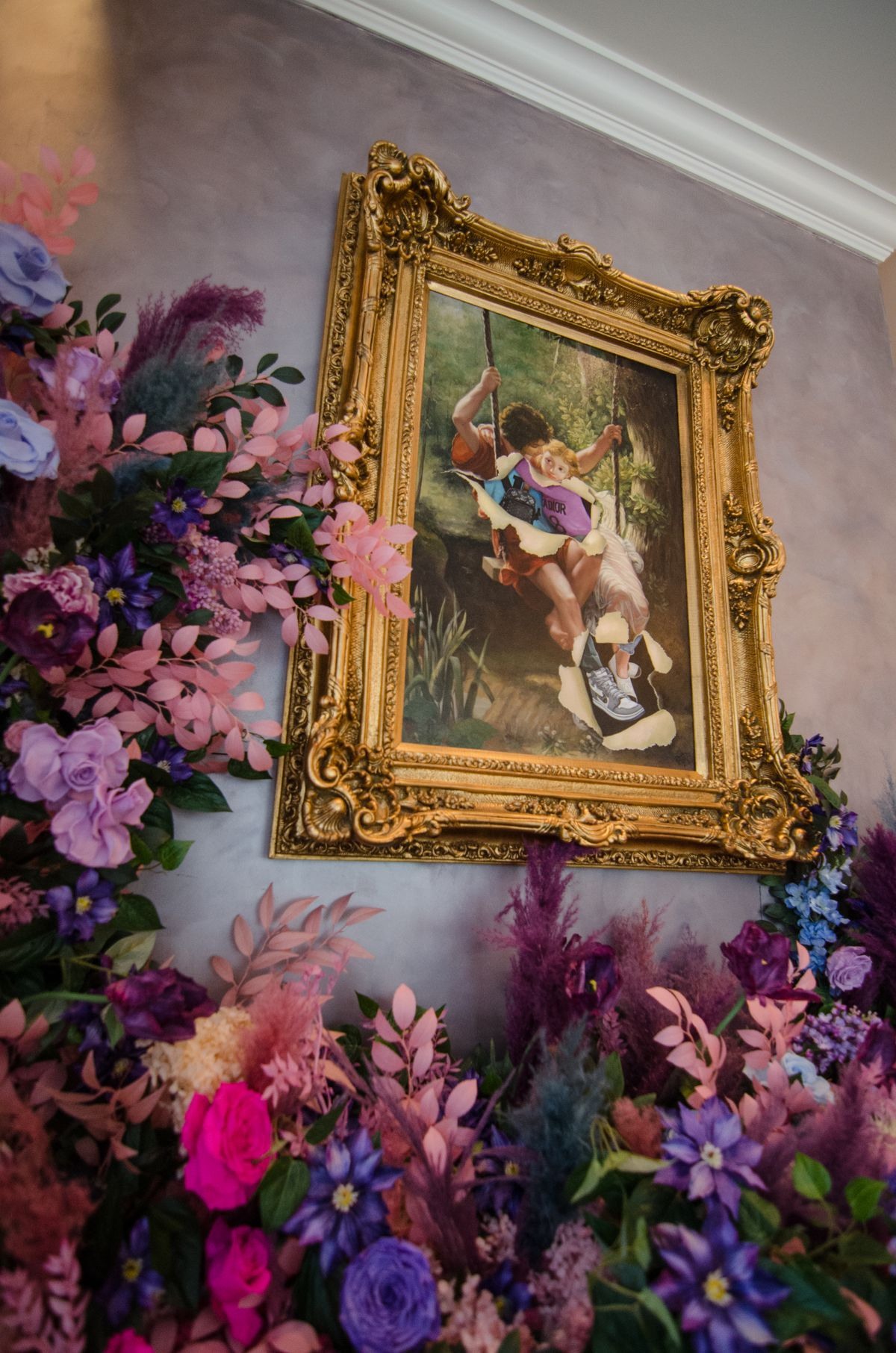 A renaissance-style painting with an elaborate gold frame is embellished with modern touches and surrounded by preserved pink and purple flowers.