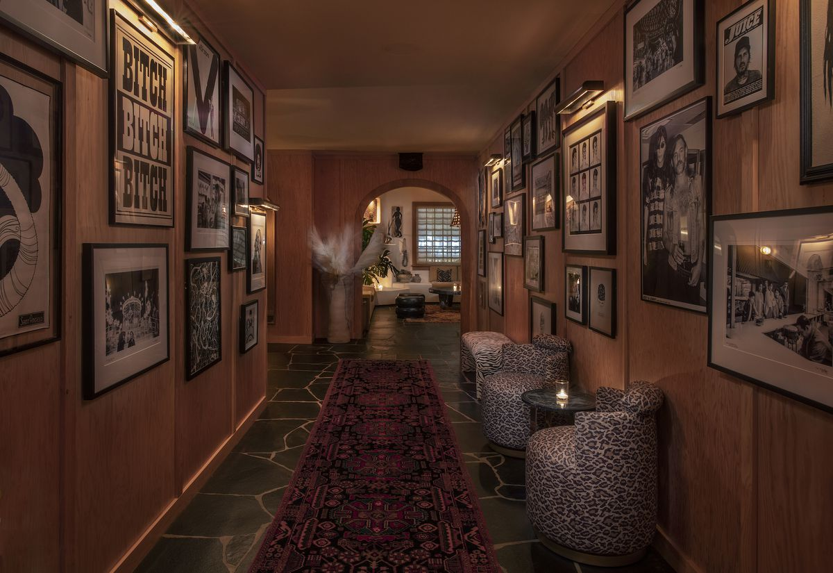 An entrance hallway to a restaurant with small hanging images and lots of rugs.