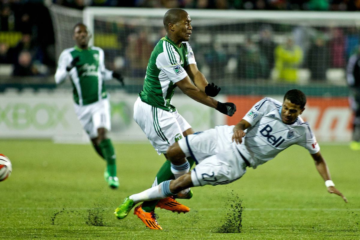 Darlington Nagbe (L) gets acquainted with the Whitecaps' Ethan Sampson (R)