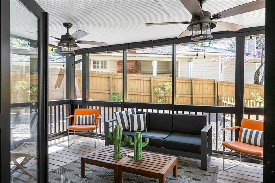 A screened porch with two ceiling fans.
