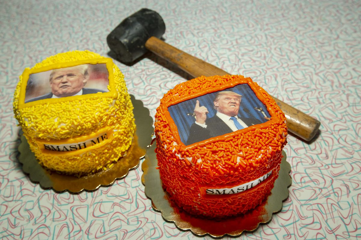 Two round cakes with orange and yellow sprinkles and Donald Trump's photo.