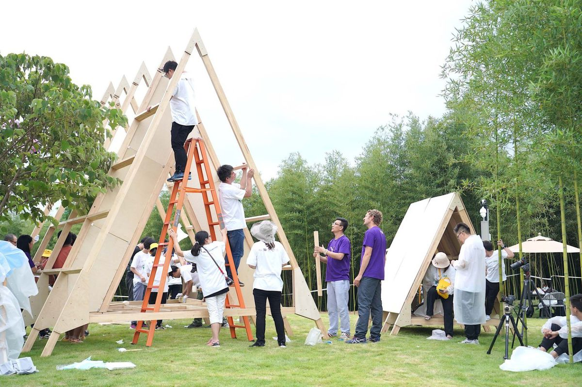 People building A-frame building.