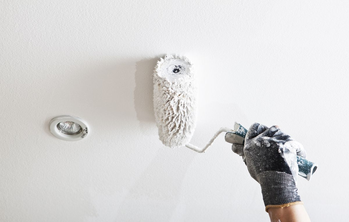 A gloved hand holding a paint roller, painting a ceiling white with an LED light in the background.