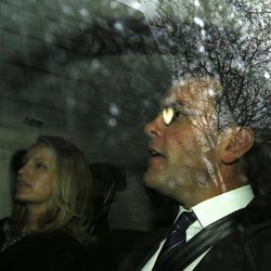James Murdoch, right, sits in the back of a vehicle with an unidentified woman as he is driven away after appearing at the Leveson Inquiry at the High Court in London, Tuesday, April 24, 2012.  James Murdoch's behind-the-scenes lobbying campaign spilled out into the public domain Tuesday as documents detailing his close ties to the British establishment were examined by a judge-led inquiry into media ethics.