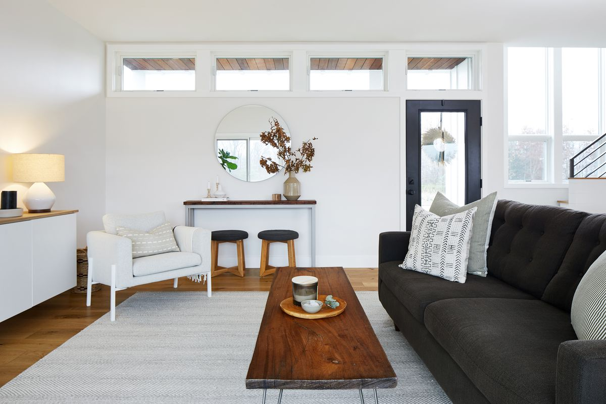 A living area with white walls and hardwood floors. There is a gray area rug and a dark gray couch. There is a white arm chair and a wooden coffee table. A mirror hangs on the far wall over a small table with two stools.