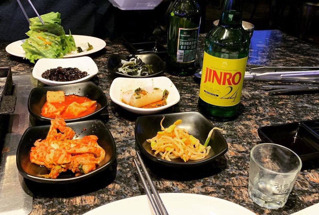 plates of banchan and a bottle of shoju