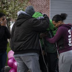 Jontae Adams hugs his father and other family members as dozens gather for a vigil for his 7-year-old daughter, Jaslyn Adams, outside the girl's grandmother's West Side home, Wednesday evening, April 21, 2021. Jaslyn was fatally shot Sunday, April 18, while in line at a McDonald's drive-thru with her father, Jontae Adams, who suffered one gunshot wound to the back and survived. Jontae Adams was released Tuesday from Stroger Hospital.