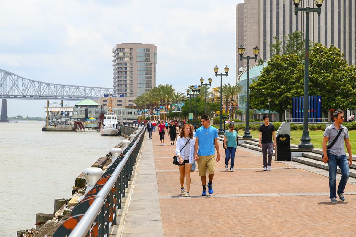 An outdoor scene of people walking down a sidewalk with the Mississippi River to the left and the Crescent City Connection and high rises in the back