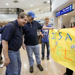 """Michael Reed is greeted at the Salt Lake City International Airport with a sign proclaiming """"Welcome! It's a boy!"""" on Friday, May 15, 2015. Reed, who was placed for adoption after his birth, recently found information on his birth father, Dennis Fay, and flew to Salt Lake City from Chicago to meet him and his siblings."""