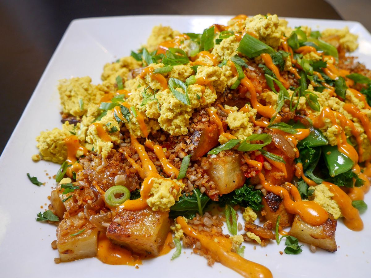"""A photo of the Blossoming Lotus scramble with tofu """"egg"""", kale, and roasted potatoes"""