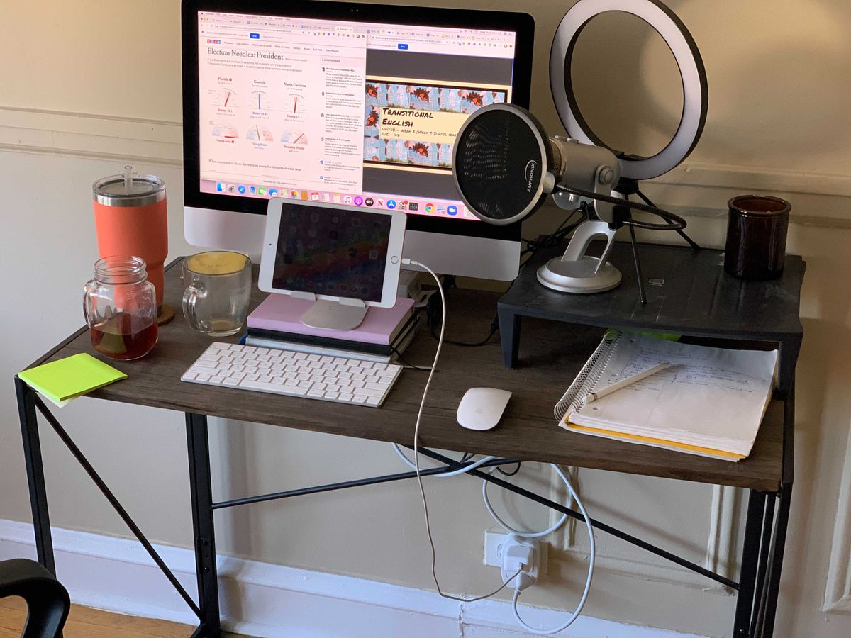 Mueze Bawany's home desk set up for virtual learning. A tablet, keyboard, monitor, microphone, and notebook atop a wooden desk.