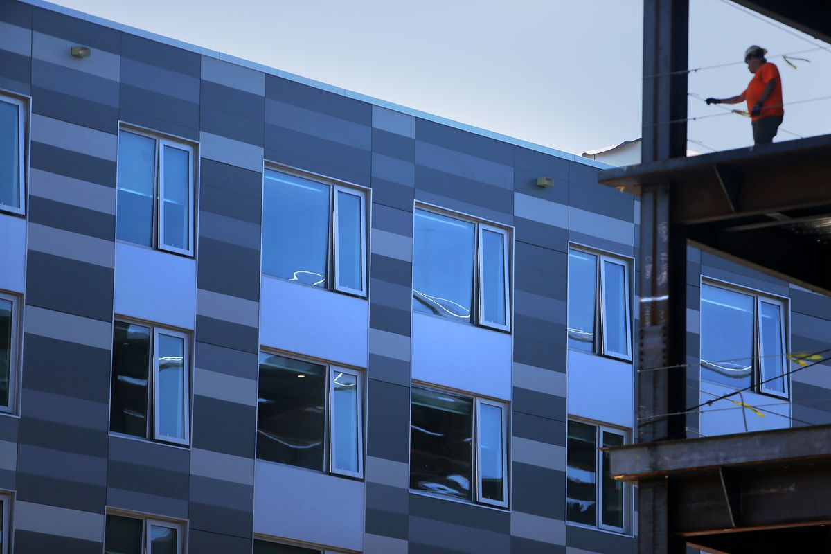 A block of newly built apartments up close, with the new windows slightly open.